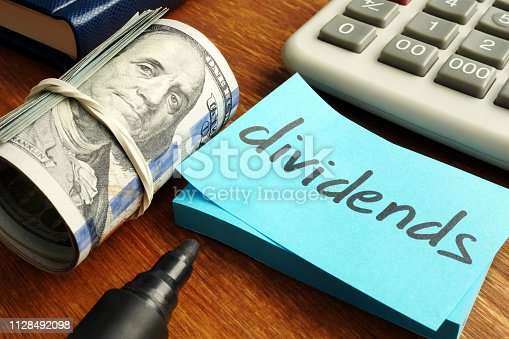 Dividends concept. Stack of dollars and calculator.