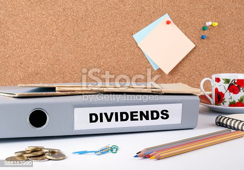Dividends - folder on white office desk.