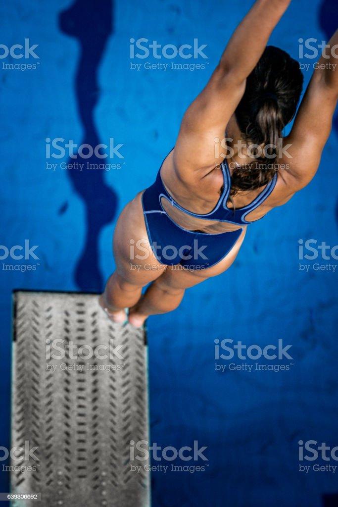 Diving competitor bouncing on the board stock photo