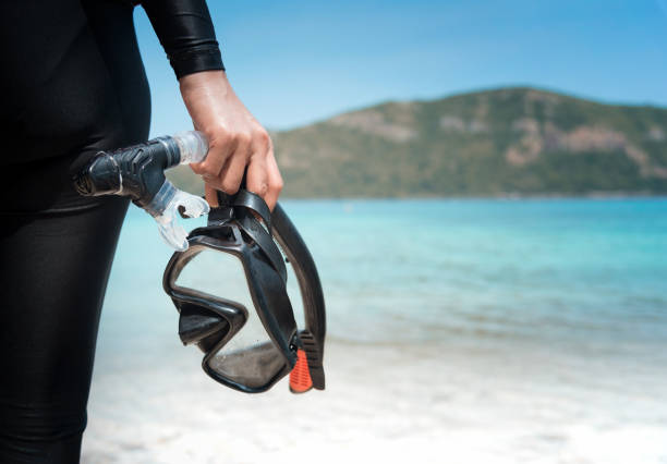 Diving goggles and snorkel gear in hand near beach stock photo