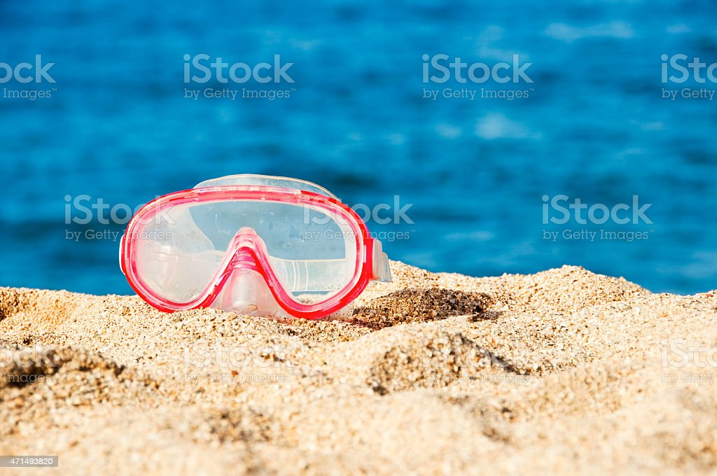 Diving mask on the sand of a beach, sea background stock photo