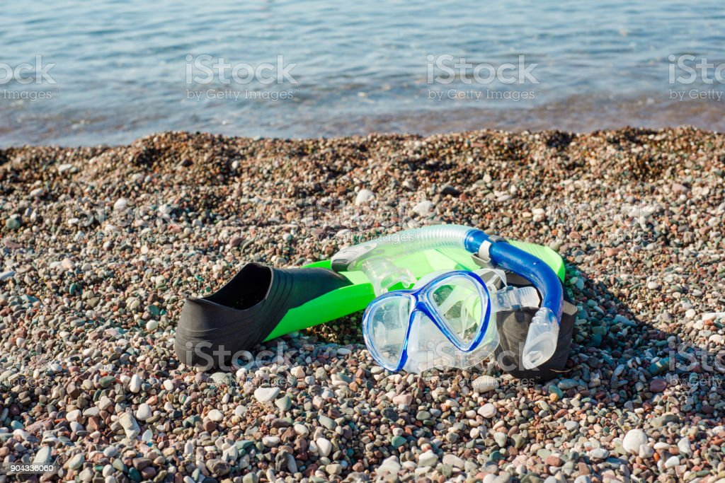 Diving mask, snorkel and fins on a beach stock photo