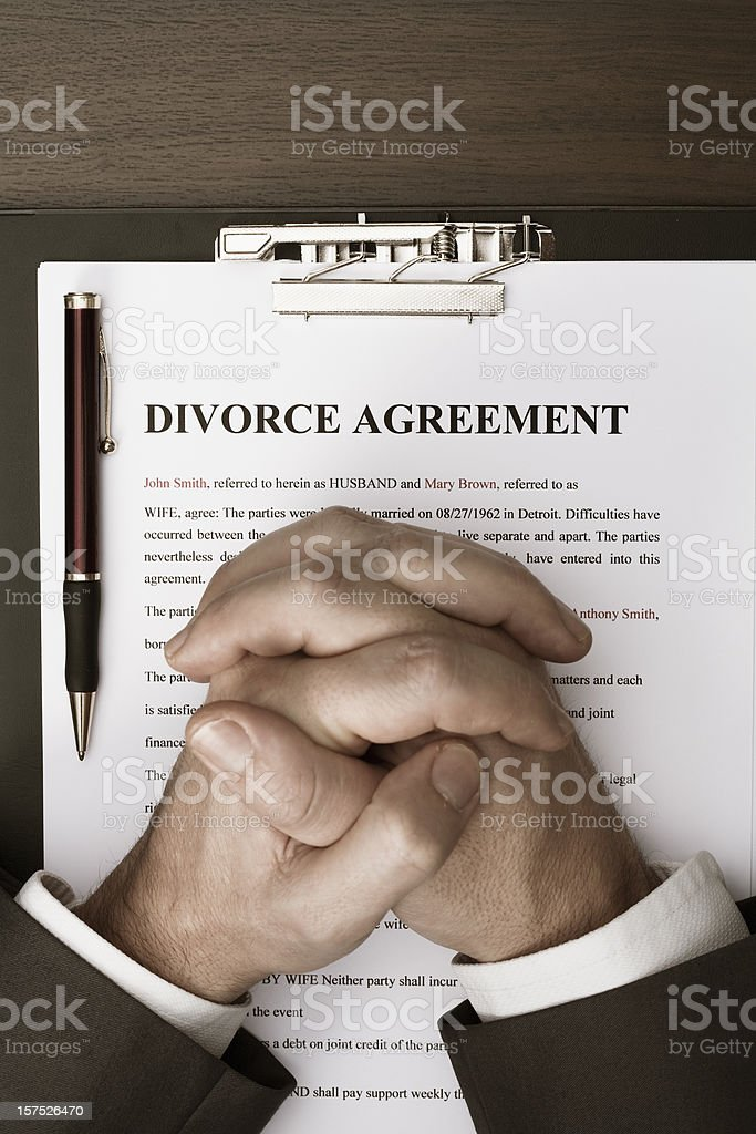 businessman with clasped hands over divorce agreement document