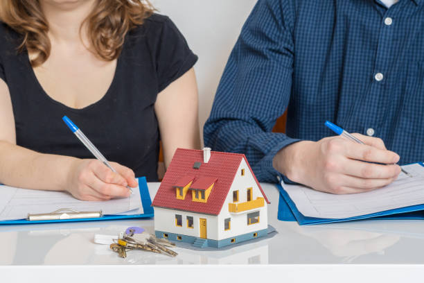 divorce and dividing a property concept. man and woman are signing divorce agreement. - divorzio foto e immagini stock