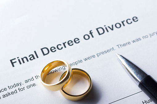 istock Divorce decree form with marriage ring and pen 926241598