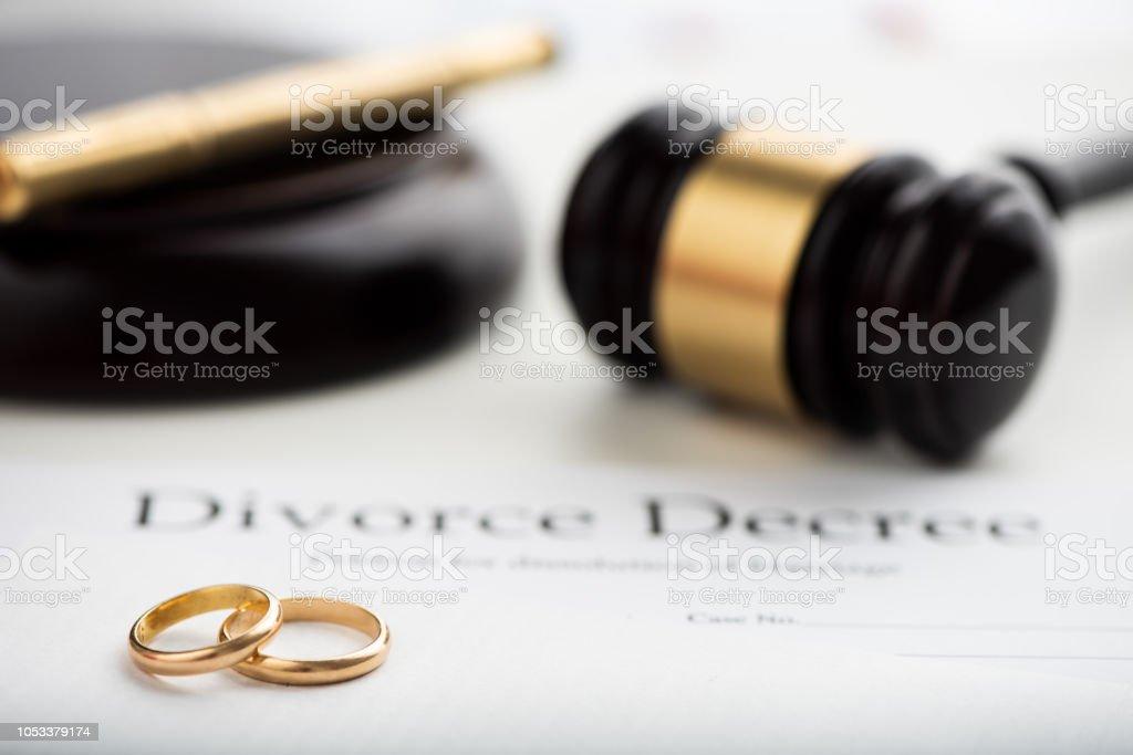Divorce decree, gavel and wedding rings. Selective focus