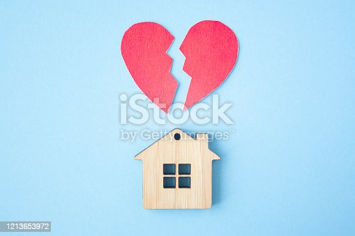 istock Divorce, division of property, poverty and no money concept. Wooden house with broken heart on bright blue background. Mortgage, rent, realtor 1213653972