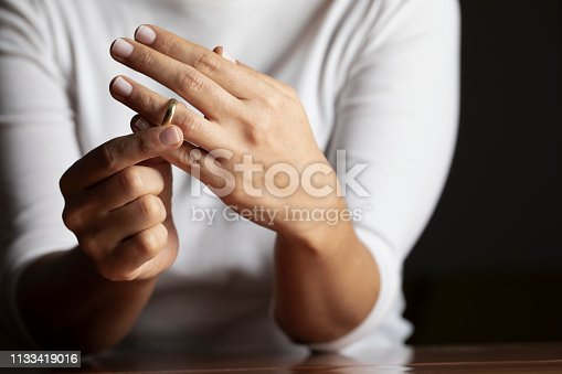 Hands of caucasian female who is about to taking off her wedding ring.