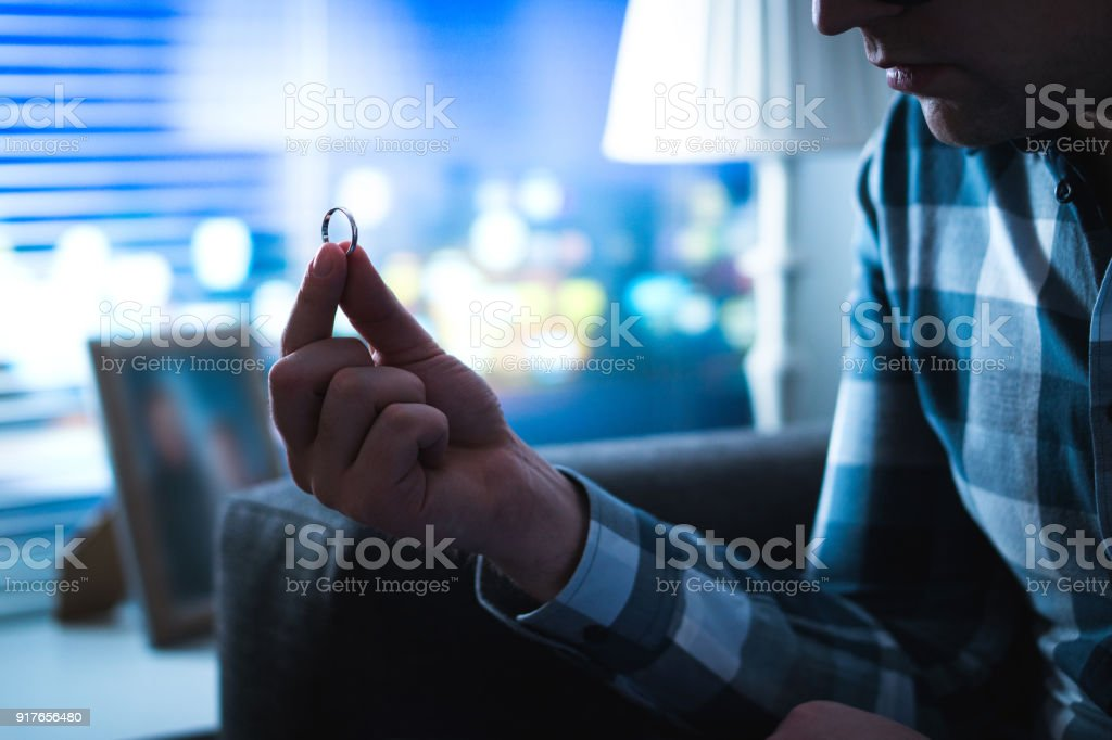 Divorcio, problemas de pareja, soltería o concepto de pesar. Hombre triste serio mirar de boda o anillo de compromiso de inicio por la noche. - foto de stock
