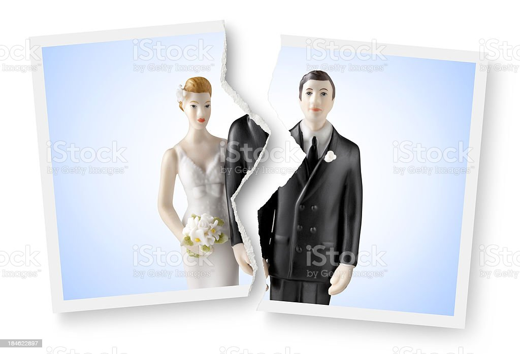 Divorce. Torn photograph of wedding cake topper. stock photo
