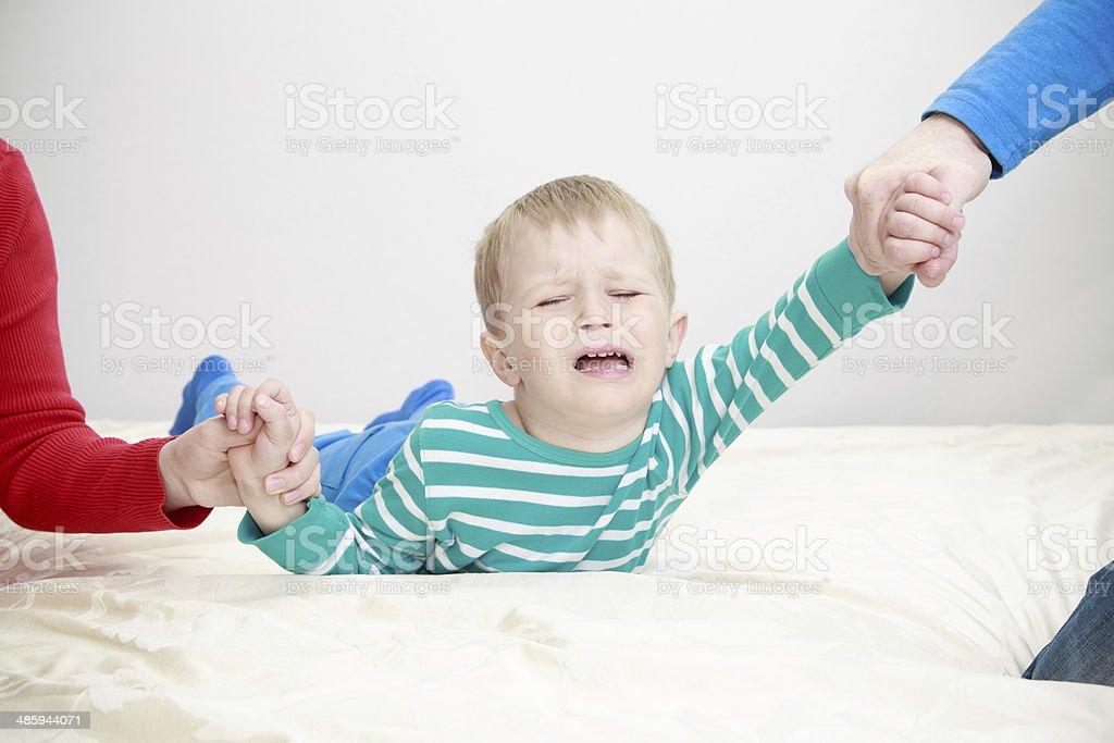 divorced parents holding sad child separately stock photo