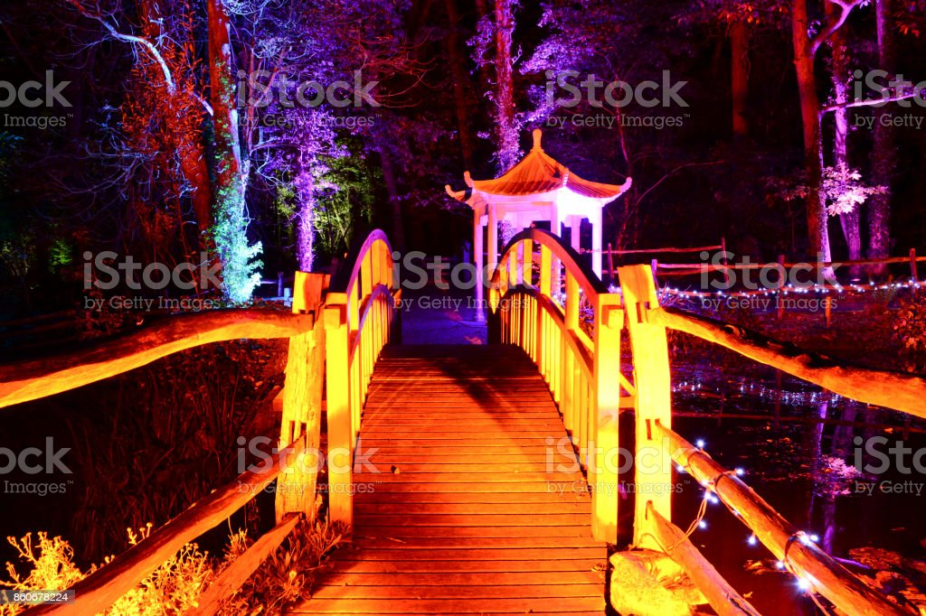 "Diwali Festival of Lights - Wooden Bridge in the Forest A wooden bridge in the forest is illuminated in celebration of the traditional Indian Diwali ""Festival of Lights"". Bridge - Built Structure Stock Photo"