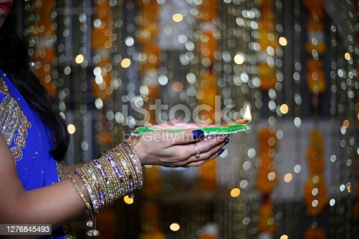 Young woman of Indian ethnicity celebrating Diwali festival and she also holding a diya in her both hands. Diwali, Deepavali or Dipavali is the Hindu festival of lights, which is celebrated every autumn in the India. One of the most popular festivals of Hinduism, Diwali symbolises the spiritual