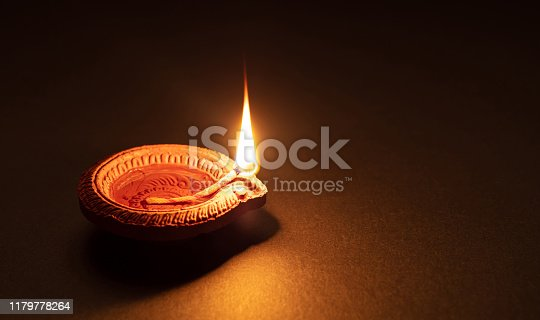 Happy Diwali. Clay diya candle illuminated in Dipavali, Hindu festival of lights. Traditional oil lamp on dark background, copy space.