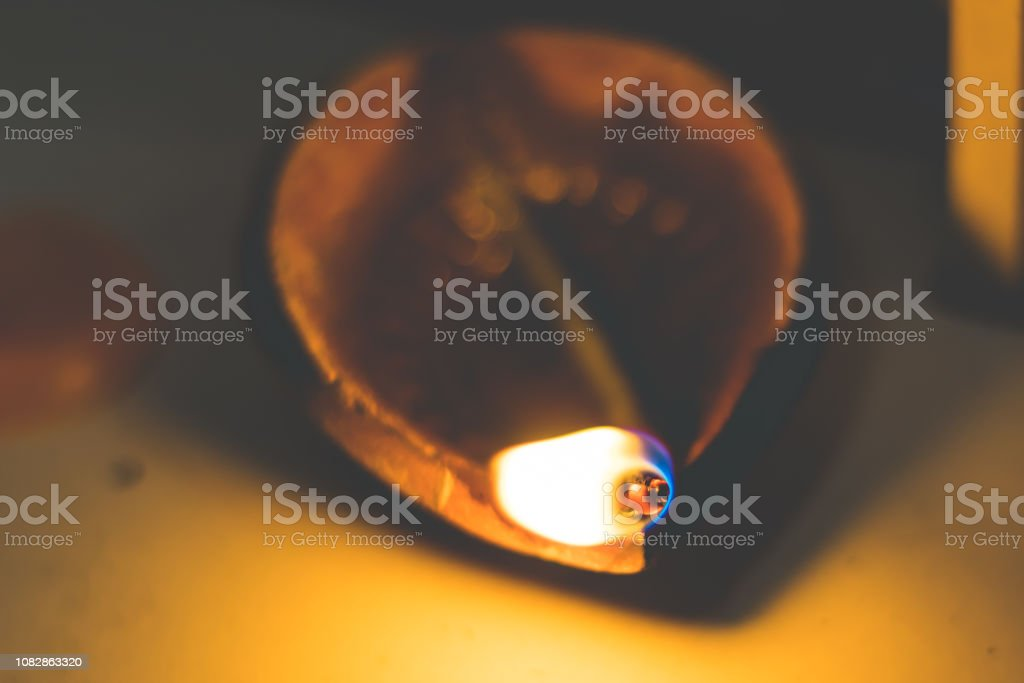 Diwali oil clay lamp also called 'Chirag' or aladdin's lamp on a dark orange black background with bright orange red flame illuminating the clay lamp. An oil lamp used as an alternative to candles stock photo
