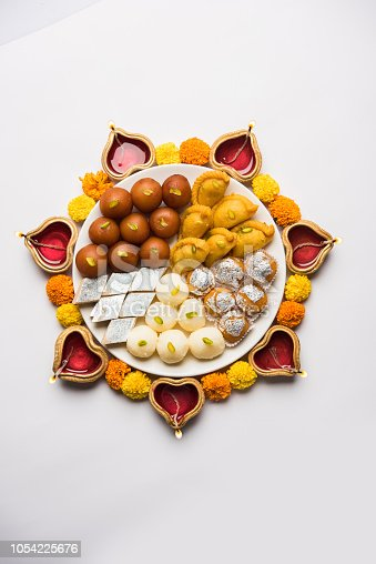 istock Diwali Rangoli made using Diya/oil lamp, flowers and plate full of Gulab Jamun, Rasgulla, kaju katli, morichoor / Bundi Laddu, Gujiya or Karanji 1054225676