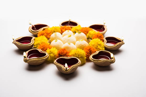 Diwali Rangoli using Diya/oil lamp, flowers and Rasgulla/rosogulla arranged over white background, selective focus stock photo