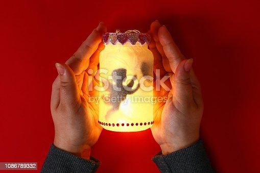 Diy Fairy Jar on red background. Gift ideas, decor February 14, St Valentines Day, love. Handmade Lamp, nightlight lantern glass jar, napkin, glue, glitter. Step by step. Process crafts. Top view