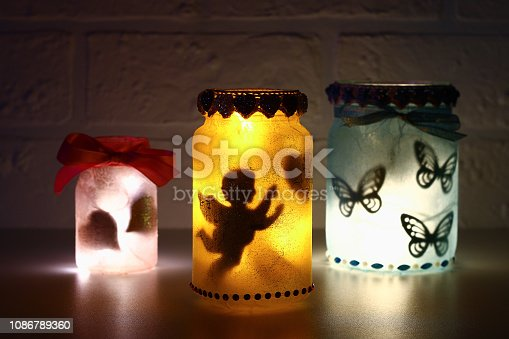 Diy Fairy Jar on white brick wall background. Gift ideas, decor St February 14, Valentines Day, love, wedding. Handmade Lamp, night light, lantern from glass jar, napkin, glue, glitter