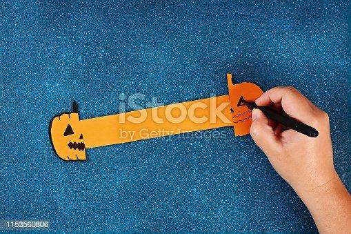 istock Diy Halloween paper bracelet pumpkin on black background. Gift idea, decor Halloween 1153560806