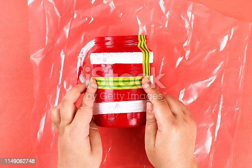 istock Diy vase 4th of July glass jar, acrylic paint, glitter, tape color American flag red blue white 1149062748