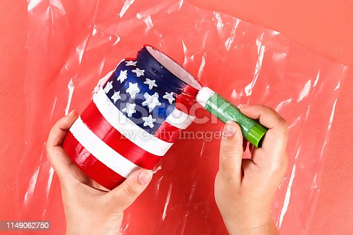 istock Diy vase 4th of July glass jar, acrylic paint, glitter, tape color American flag red blue white 1149062750