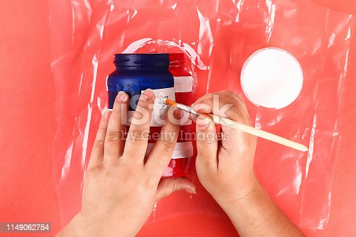 istock Diy vase 4th of July glass jar, acrylic paint, glitter, tape color American flag red blue white 1149062754