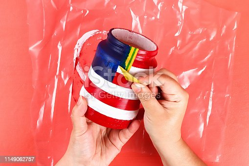 istock Diy vase 4th of July glass jar, acrylic paint, glitter, tape color American flag red blue white 1149062757
