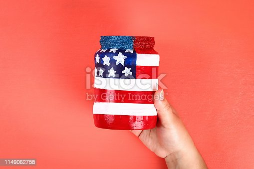 istock Diy vase 4th of July glass jar, acrylic paint, glitter, tape color American flag red blue white 1149062758