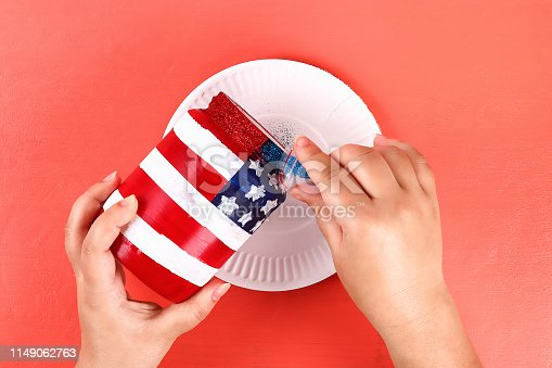 istock Diy vase 4th of July glass jar, acrylic paint, glitter, tape color American flag red blue white 1149062763