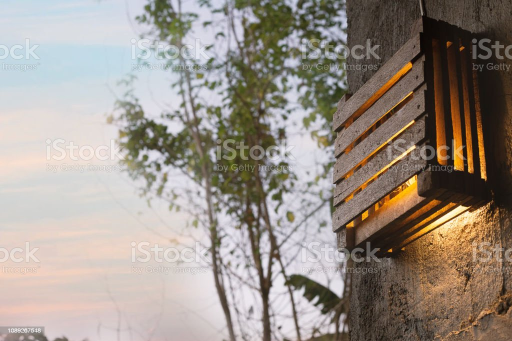 Diy wood lamp on wall in morning time. stock photo