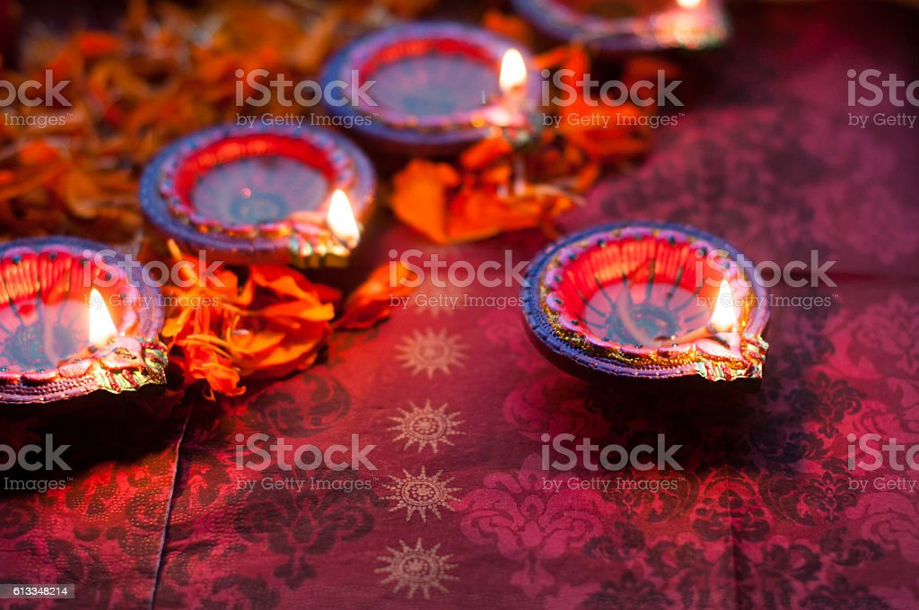 diya lamps lit during diwali celebration with flowers stock photo