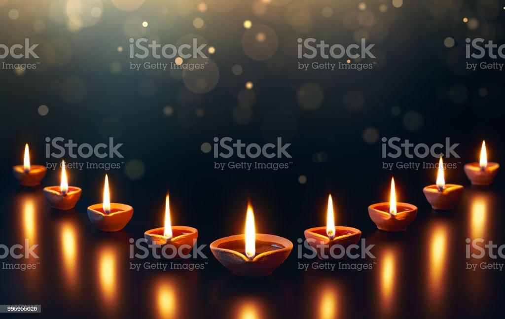 Lâmpadas de Diya sobre uma base reflexiva com bokeh brilhante - foto de acervo
