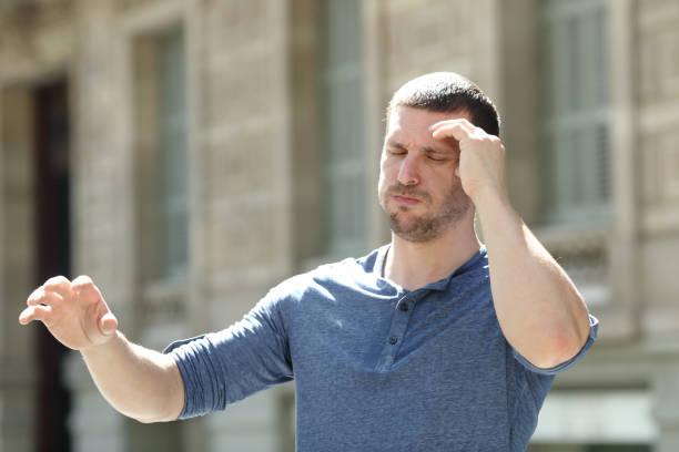 dizzy erwachsenen mann leidet kopfschmerzen auf der straße - höhenangst stock-fotos und bilder