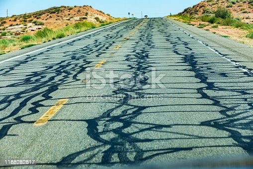 Dizzy streams of blacktop tar poured hot onto a rural highway to repair numerous cracks in the aging asphalt road surface. Car point of view looking up a hill incline at the headlights of an approaching car just coming over the horizon at the top edge of the road.