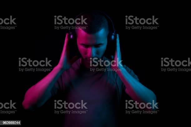 Dj holding his head set on black background under magenta and blue picture id962669244?b=1&k=6&m=962669244&s=612x612&h=aio4k6msbjezzffkrh409 8hly54rxcqbfi2fljbo i=