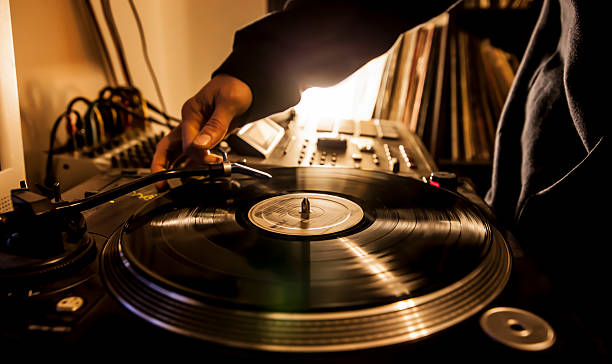 Dj in studio with turntable Dj in studio puts needle on record. radio dj stock pictures, royalty-free photos & images