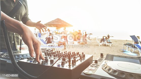 istock Dj mixing at sunset beach party in summer vacation outdoor - Disc jockey hands playing music for tourist people in chiringuito kiosk bar - Event, music and fun concept - Focus on right hand 1143248555