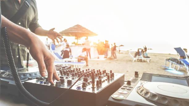dj mixen bij sunset beach party in de zomervakantie buiten-disc jockey handen spelen van muziek voor toeristische mensen in chiringuito kiosk bar-evenement, muziek en fun concept-focus op rechterhand - strandfeest stockfoto's en -beelden