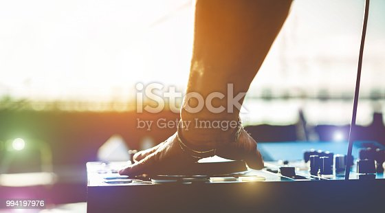 istock Dj mixing music outdoor at beach boat party festival  - Summer nightlife view of disco club at sunset - Focus on hand - Fun, millennials generation, youth lifestyle,entertainment and fest concept 994197976