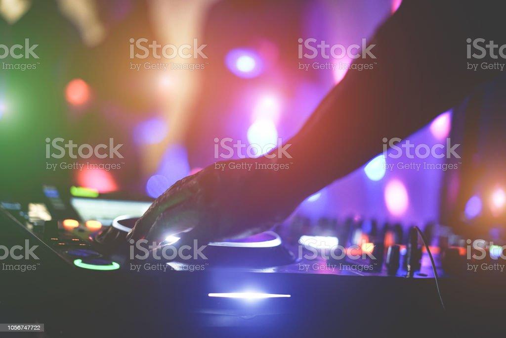 DJ mixen buiten op strand partij festival met de menigte van mensen in de achtergrond - zomer nachtleven bekijken van disco club buiten - Soft focus aan kant vingers - Fun, jeugd, entertainment en fest concept foto