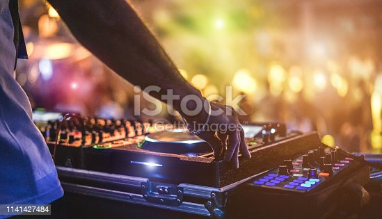 istock Dj mixing outdoor at beach party festival with crowd of people in background - Summer nightlife view of disco club outside - Soft focus on hand - Fun ,youth,entertainment and fest concept 1141427484