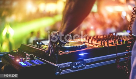 istock Dj mixing outdoor at beach party festival with crowd of people in background - Summer nightlife view of disco club outside - Soft focus on hand fingers - Fun ,youth,entertainment and fest concept 1145412057