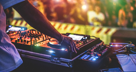 Dj mixing outdoor at new year party festival with crowd of people in background - Nightlife view of disco club outside - Soft focus on bracelet, hand - Fun ,youth,entertainment and fest concept