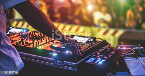 istock Dj mixing outdoor at new year party festival with crowd of people in background - Nightlife view of disco club outside - Soft focus on bracelet, hand - Fun ,youth,entertainment and fest concept 1191407748