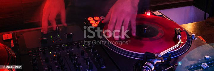 hand of dj on vinyl disk in red light panorma