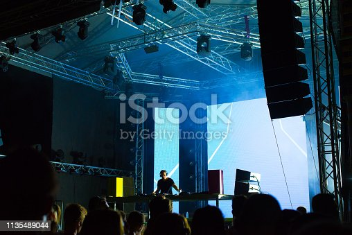 Dj playing techno music on the stage during the night concert.