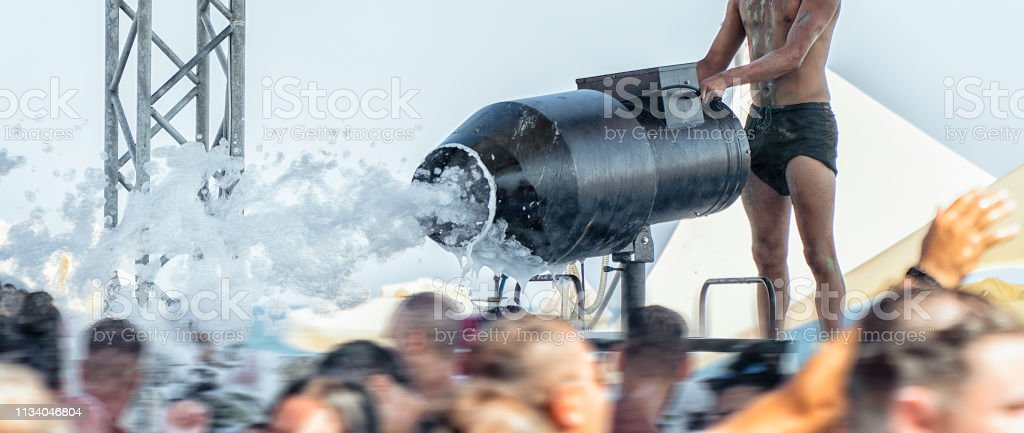 Dj using foam machine at foam party on the beach in music festival stock photo