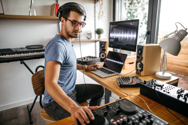 Dj working on digital mixing control at home recording studio Young man recording new music using laptop and digital mixing control at home studio producer stock pictures, royalty-free photos & images