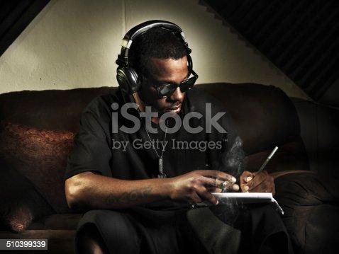 istock dj writing lyrics on note book in studio 510399339